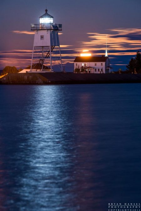 the full moon rises over the Grand Marais lighthouse and Coast Guard station