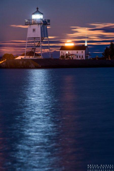 the full moon rises over the Grand Marais lighthouse and Coast Guard station