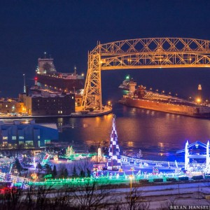 The Great Lakes Trader & Joyce L. VanEnkevort barge and tug combo is followed by the Thunder Bay under the Duluth Lift Bridge with Bentleyville in the foreground. Minnesota.