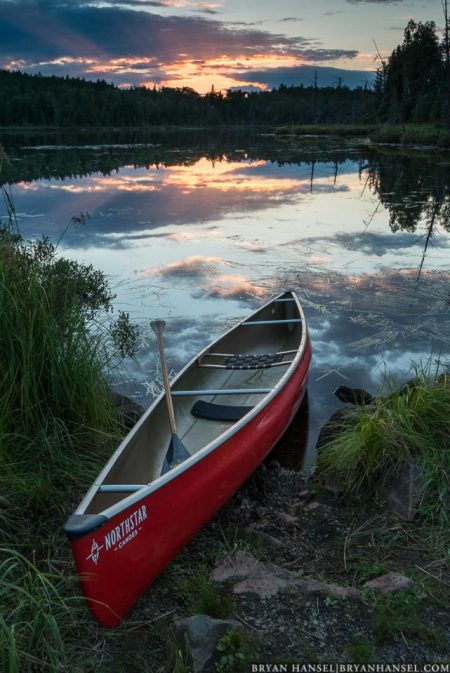 A canoe on swamper awaits a paddler at sunset