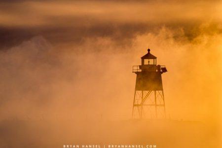 Grand Marais lighthouse and sea smoke in winter at sunrise.