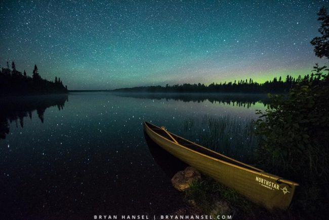 canoe under the northern lights and low level lighting