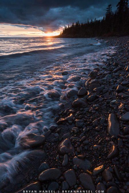 sunset over lake superior on cobblestone beach
